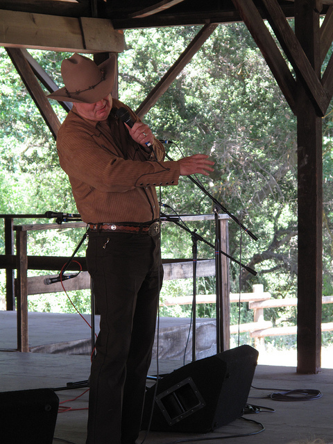 I like this photo, despite the hidden face of the poet,because it appears to show him in a dramatic gesture, like he's really got his heart into the performance. Also, the  mesquite tree and bright sunlight in the background resonate as a Texas scene, although it could be in New Mexico.
