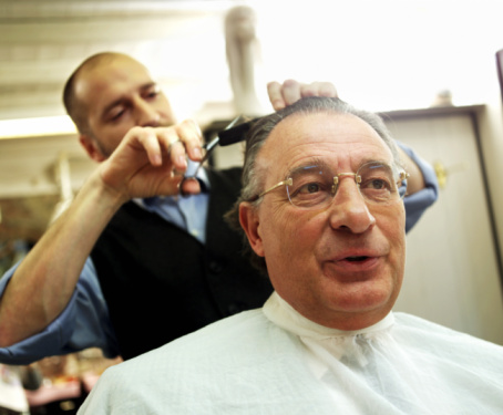 Barber cutting hair of mature man